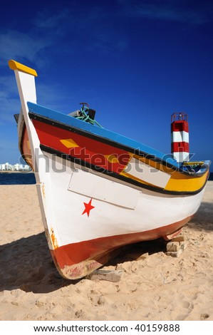Portuguese fishing boat on the beach - stock photo
