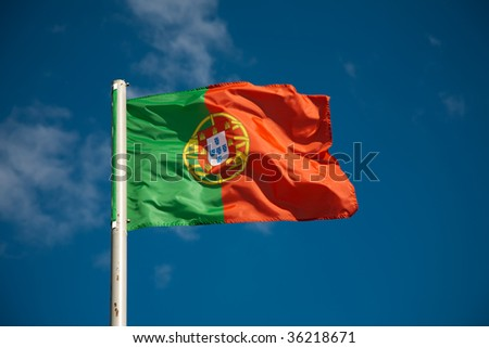 Portuguese flag against blue sky - stock photo