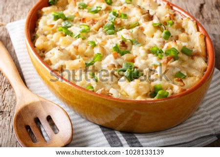 Portuguese food: casserole with cod, potatoes, onions and cream in a baking dish close-up on the table. horizontal