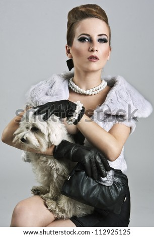 Posh, rich lady is holding a sweet maltese dog - stock photo