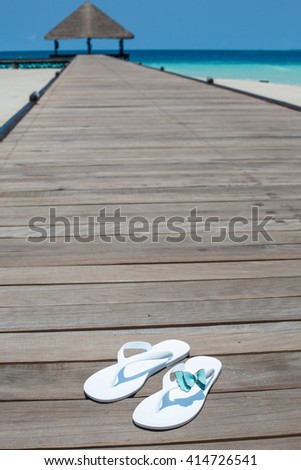 posh vacation on the island paradise. Maldives. view of the white sand clean blue azure ocean water with wooden decking jetty - stock photo