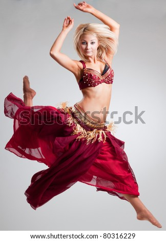 Posing in motion bellydancer, studio isolated shot - stock photo