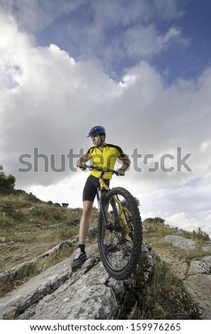 Posing man on bike in outdoor wide angle portrait - stock photo