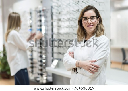 Posing optometrist woman in eyeglasses store smiling looking at camera