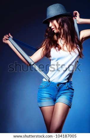 posing sexy woman in hat and shorts with suspenders in hands - stock photo
