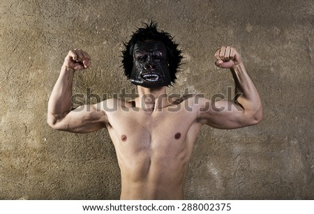 Posing strong man with monkey mask showing muscles.