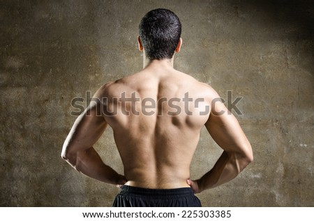 Posing strong young man with arms on hip on dirty wall background