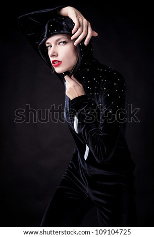 Posing woman in fashionable costume on dark background.