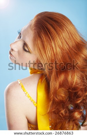 Posing woman with beautiful red hair on blue background - stock photo