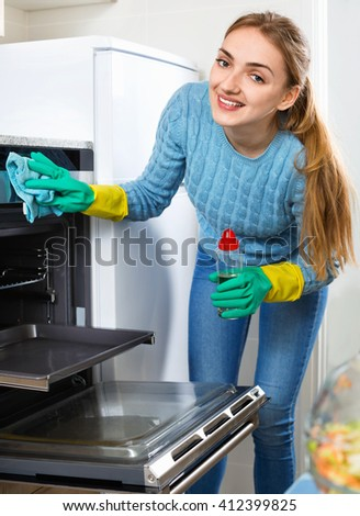 Positive adult girl in gloves removing snuff in oven  - stock photo