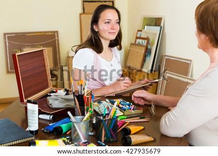 Positive adult girl paints a portrait of a mature woman - stock photo