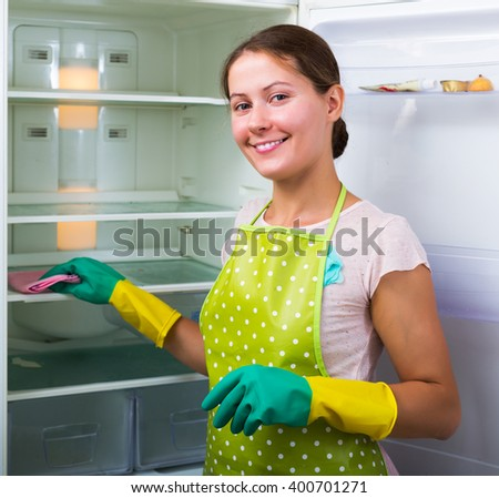 Positive adult housewife cleaning refrigerator inside and smiling - stock photo