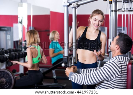 Positive adults of different age having strength training in sport club