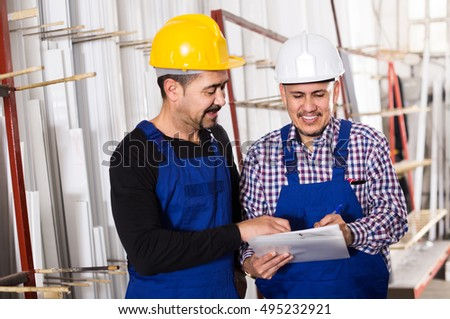 positive american mechanical engineer inspecting the work of labour at modern factory