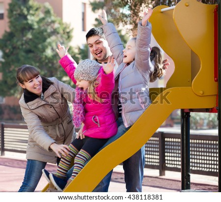 positive american parents playing with little daughters at slide of playground - stock photo