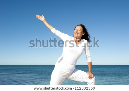Positive and cheerful, attractive looking senior woman enjoying lifestyle and retirement fit and healthy, isolated with ocean and sky as background and copy space. - stock photo