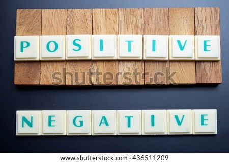 Positive and Negative concept. The words spelled by letters with wood block on blackboard. Space for texts. Dark tone. - stock photo
