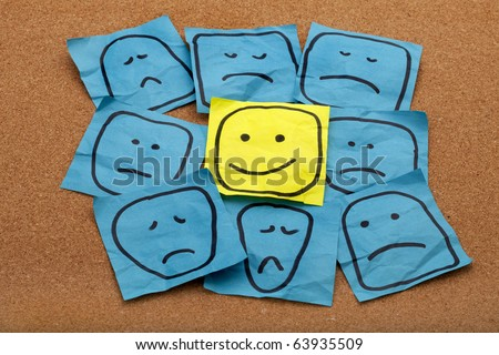 positive attitude or optimism concept - happy smiley face on yellow sticky note surrounded by sad unhappy blue faces