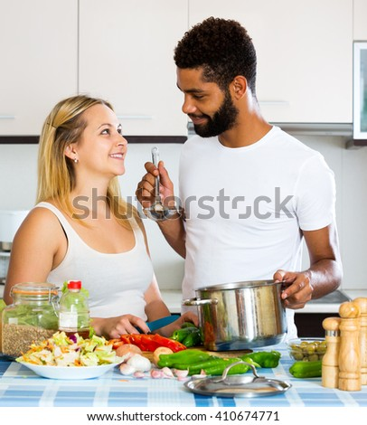 Positive black husband helping young white woman preparing healthy dinner - stock photo