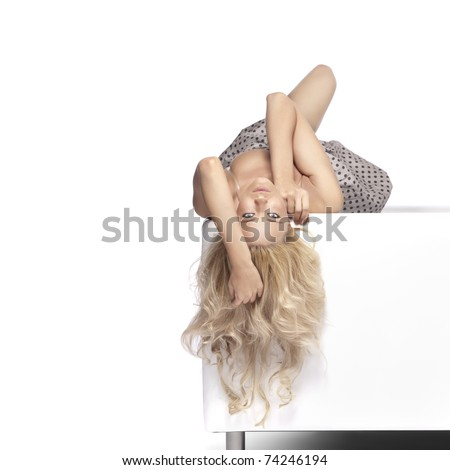 Positive blonde woman laying on a white leather couch. - stock photo