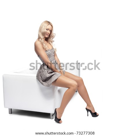 Positive blonde woman stting on a white leather couch. - stock photo