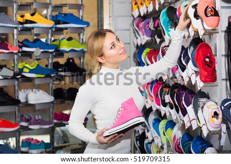 Positive blonde young girl choosing shoes in the sport store