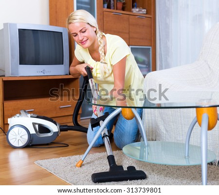 Positive blonde young woman hoovering in living room and smiling - stock photo