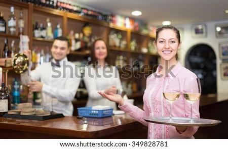 Positive brunette waitress and barmen working in modern bar - stock photo