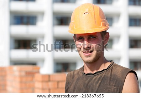 Positive builder man worker with hard hat at construction site background - stock photo