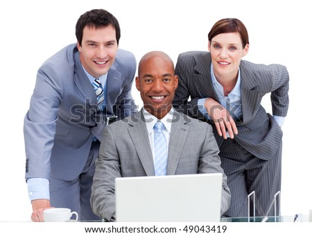 Positive business co-workers using a laptop in the office - stock photo