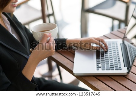 Positive business lady using her laptop and drinking tea - stock photo