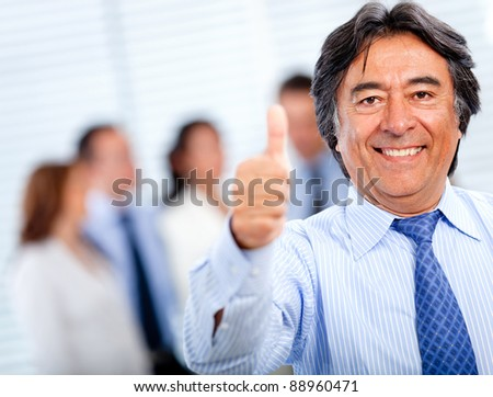 Positive business man with thumbs-up at the office - stock photo