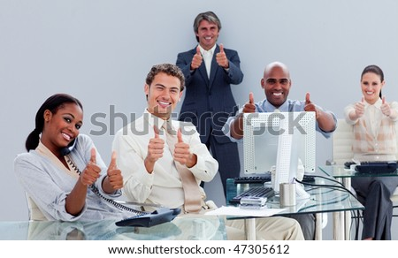 Positive business team celebrating a success in the office - stock photo