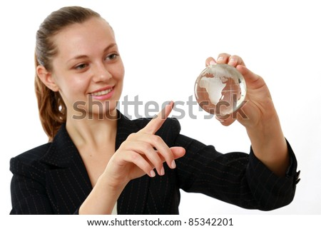 Positive businesswoman pointing on a glass globe in her hand, isolated on white