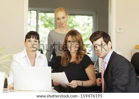 Positive businesswoman sitting with her team while they are using a laptop in a meeting