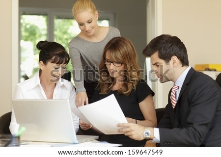 Positive businesswoman sitting with her team while they are using a laptop in a meeting - stock photo