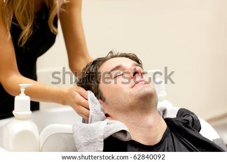 Positive caucasian man shampooed in a hairdressing salon - stock photo