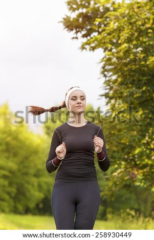 Positive Caucasian Sportswoman In Forest Jogging. Vertical Image Composition - stock photo