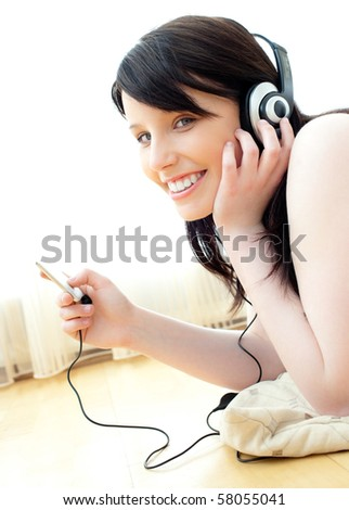 Positive caucasian teenager listen to music lying on the floor in the living room - stock photo