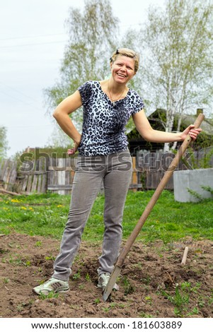Positive cheerful blonde with a shovel in the spring garden