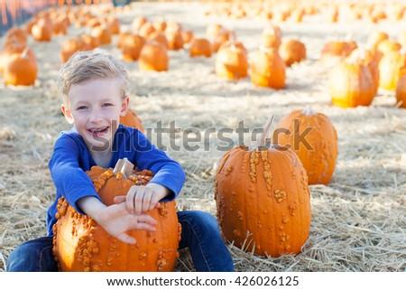 positive cheerful boy enjoying pumpkin patch at fall being playful  - stock photo