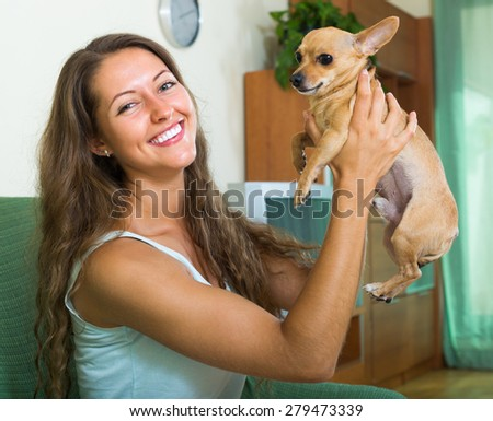 Positive cheerful smiling girl with Russian Toy in arms at home