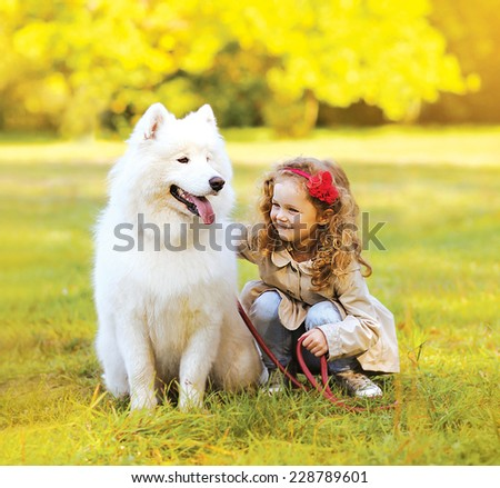 Positive child and dog having fun outdoors in the park - stock photo