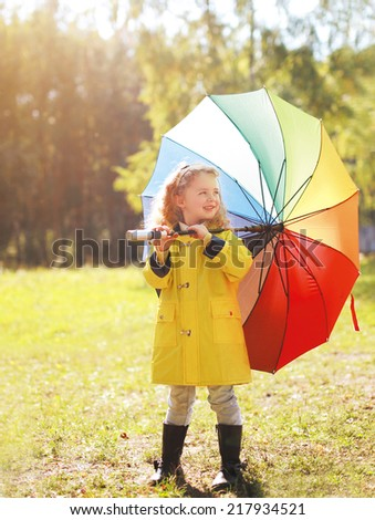Positive child with colorful umbrella in autumn day - stock photo