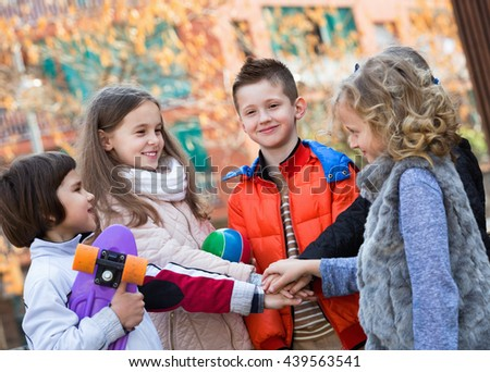Positive children holding hands and giving friendship vow - stock photo