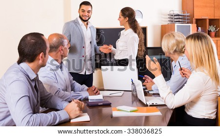 Positive colleagues at working meeting in office with diagram at background  - stock photo