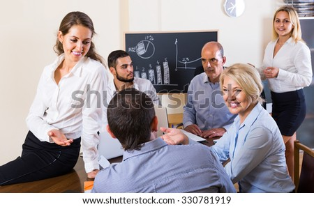 Positive colleagues discussing price development at office - stock photo