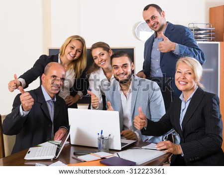 positive colleagues looking at laptop and smiling
