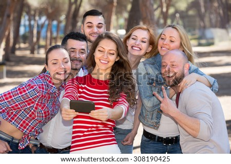 Positive colleagues taking mutual photo at summer picnic outdoor