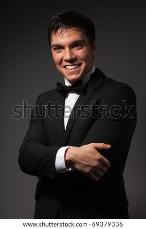 Positive confident businessman wearing formal suit and looking at camera